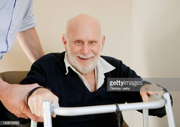 smiling older man using walker - vulnerability stock pictures, royalty-free photos & images