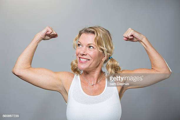 Smiling older woman flexing biceps
