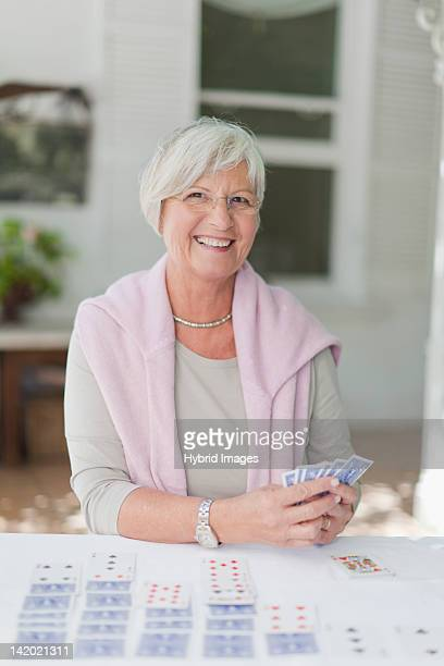 Smiling older woman playing cards