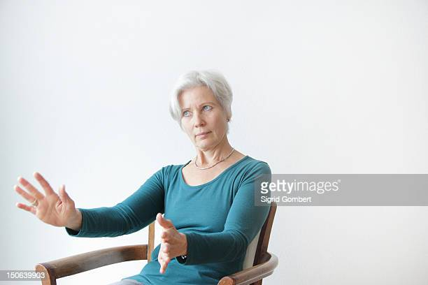 Smiling older woman reaching in chair