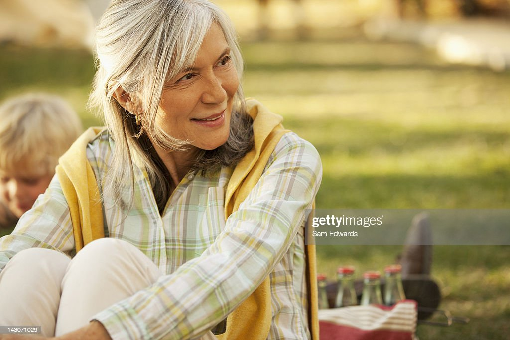 Smiling older woman relaxing outdoors : Stock Photo