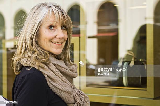 smiling older woman window shopping - 60 64 years stock pictures, royalty-free photos & images