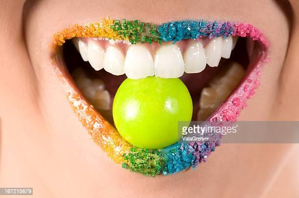 Lächelnd offenem Mund mit grünen gumball zwischen den Zähnen.