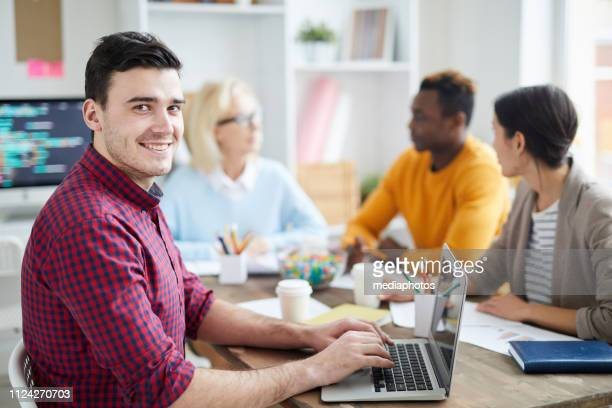 Smiling optimistic handsome young man with stubble sitting at table and looking at camera while typing on laptop at meeting