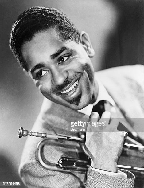 Smiling orchestra leader Dizzy Gillespie poses brightly with his trumpet