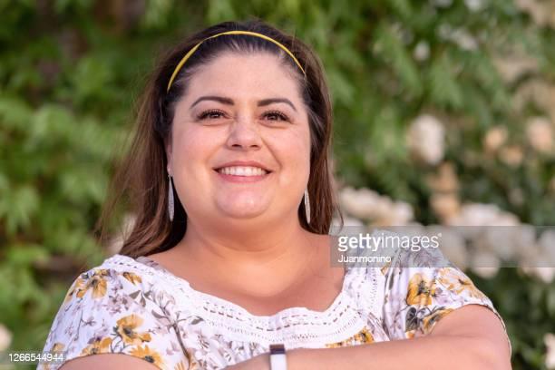 glimlachende te zware spaanse vrouw - mid adult women stockfoto's en -beelden