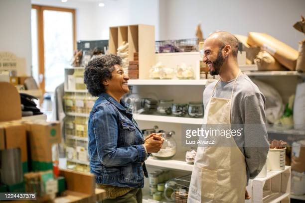 smiling owner and customer laughing at illuminated zero waste store - small business stock pictures, royalty-free photos & images