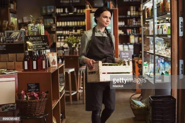 smiling owner carrying vegetable crate while walking in store - plank meubels stockfoto's en -beelden