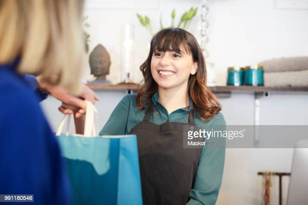 Smiling owner giving shopping bag to female customer at store