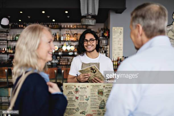 Smiling owner looking at mature couple with menu in restaurant