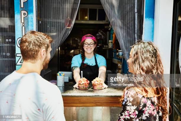 smiling owner of juice bar serving organic acai bowls to customers sitting at bar - small business stock pictures, royalty-free photos & images