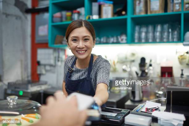 Smiling owner receiving payment at cafeteria