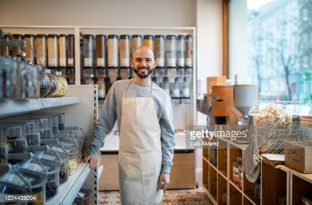 smiling owner standing by rack at zero waste store - apron stock pictures, royalty-free photos & images