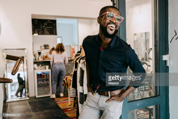 smiling owner with hands in pockets standing at doorway of clothing store - owner stock pictures, royalty-free photos & images