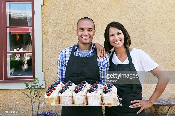 Smiling owners standing with tray of pastries outside cafe