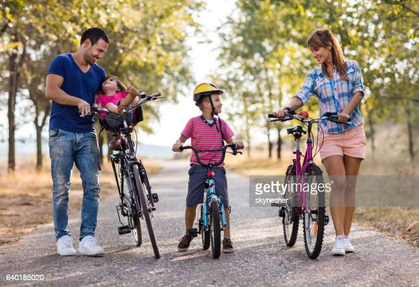 Smiling parents and children with bicycles in the park.