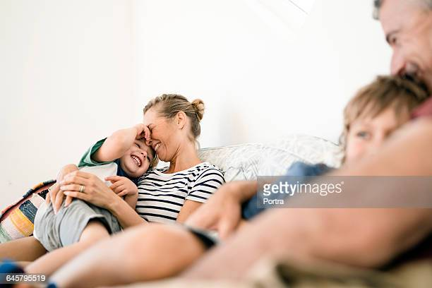 smiling parents are embracing sons at home - biparental fotografías e imágenes de stock