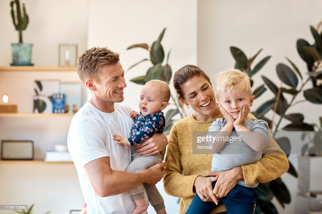 Smiling parents carrying children at home : Stock Photo