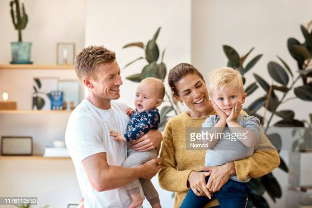 smiling parents carrying children at home - home interior stock pictures, royalty-free photos & images