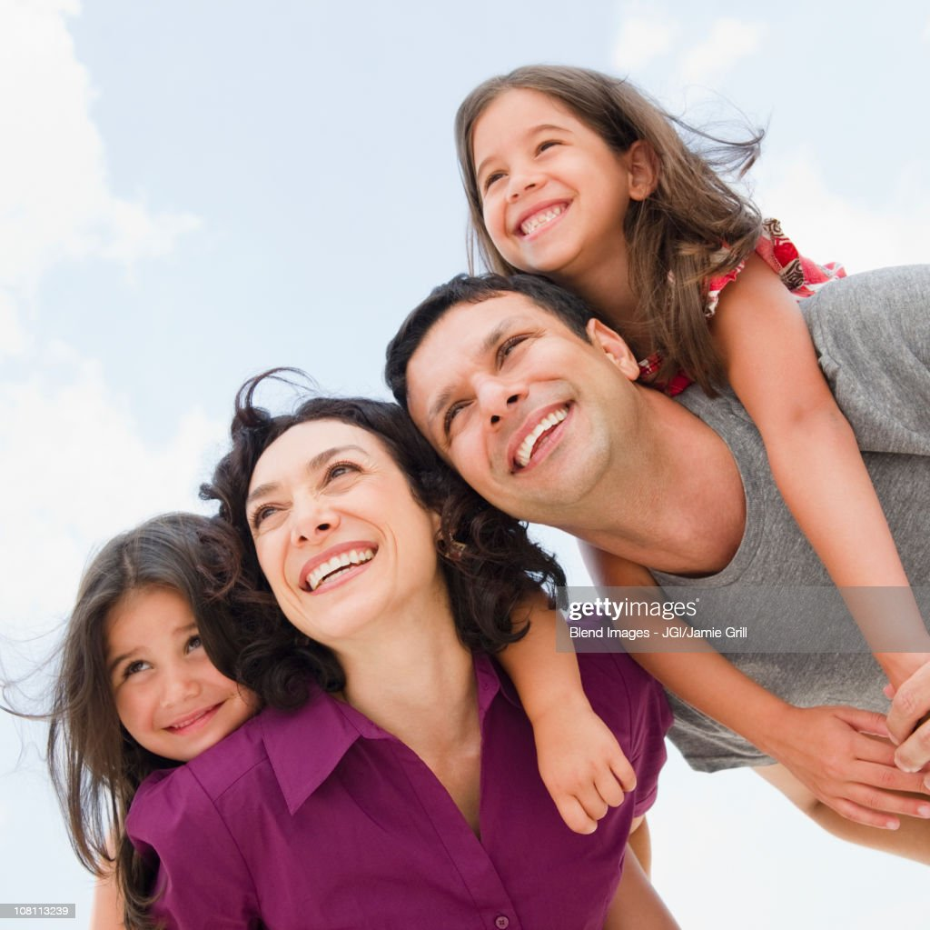 Smiling parents giving daughter's piggyback ride : Stock Photo