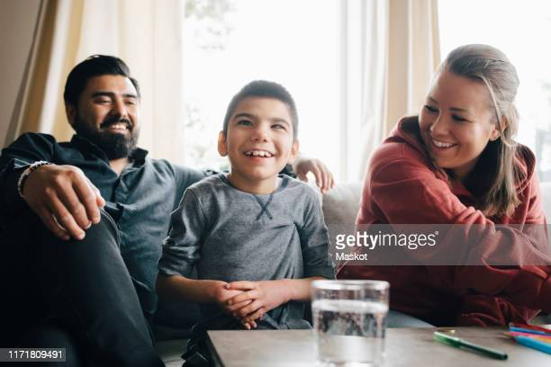 smiling parents looking at autistic son while sitting on sofa in living room - differing abilities fotografías e imágenes de stock