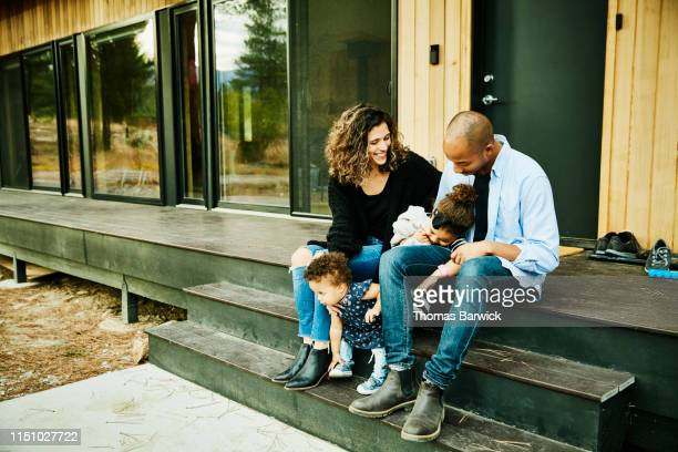 smiling parents sitting with two young daughters on porch of cabin - mid adult stock pictures, royalty-free photos & images