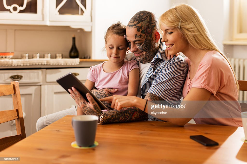 Smiling parents surfing the Internet with daughter on touchpad. : Stock Photo
