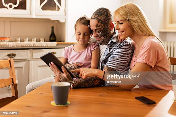 smiling parents surfing the internet with daughter on touchpad. - adult stock pictures, royalty-free photos & images