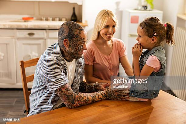 Smiling parents talking to their daughter in the kitchen.