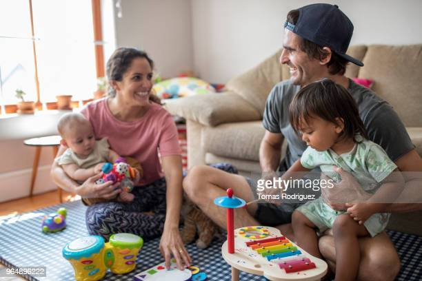 Smiling parents with a baby and toddler on their laps playing together in the living room