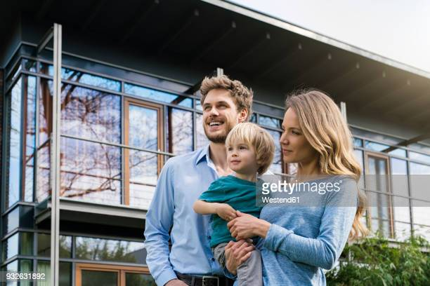 smiling parents with son in front of their home - ricchezza foto e immagini stock