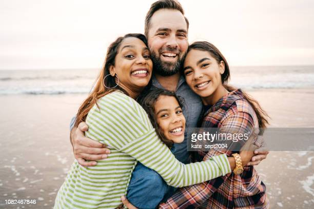 smiling parents with two children - multiracial group stock pictures, royalty-free photos & images