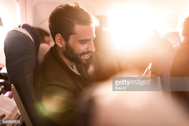 Smiling passenger text messaging on cell phone in the airplane.