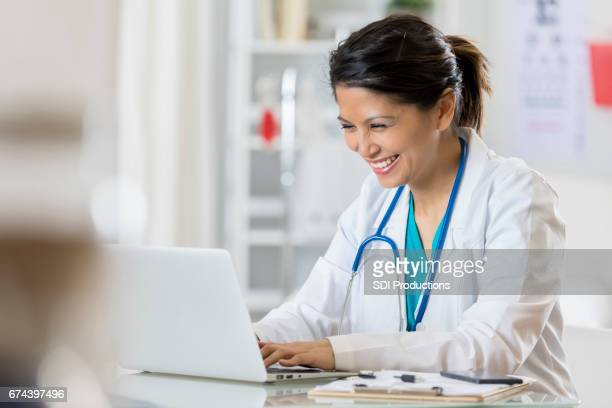 Smiling pediatrician uses computer in her office