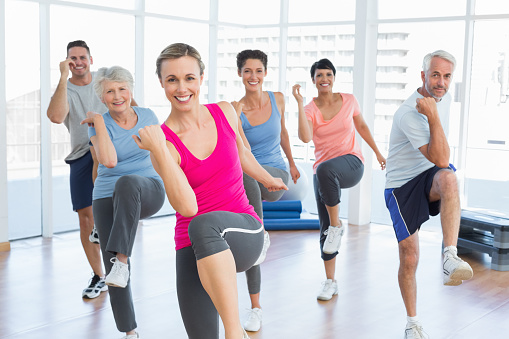 Smiling people doing power fitness exercise at yoga class 693103622