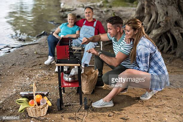 Smiling people having a barbecue during day in nature.