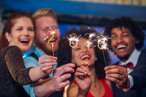 Smiling people holding sparklers 1179065744