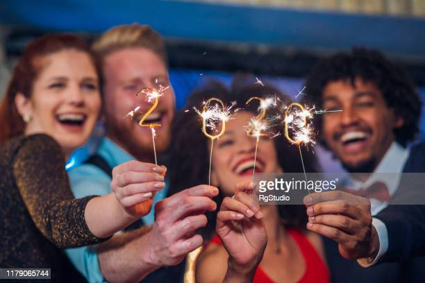 smiling people holding sparklers - new year's eve stock pictures, royalty-free photos & images