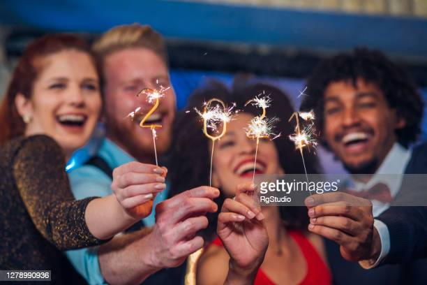 smiling people holding sparklers - 2021 stock pictures, royalty-free photos & images
