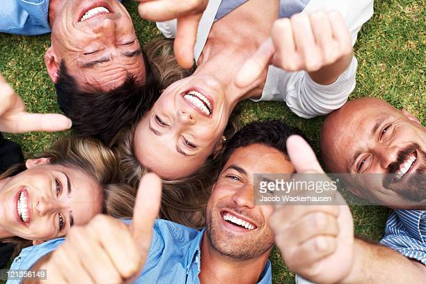Smiling people lying on the grass with thumbs up