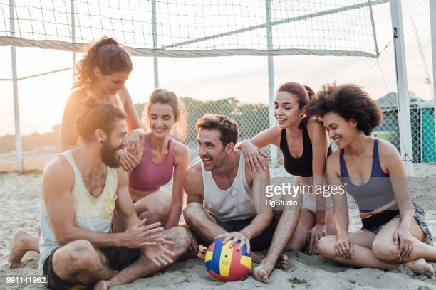 Smiling people resting at the beach after a game of volleyball