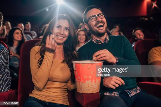 lächelnde menschen mit popcorn im kino - filmfestival stock-fotos und bilder