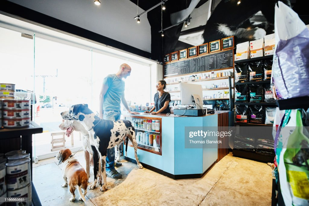 Smiling pet store owner helping customer with dogs check out : Stock Photo