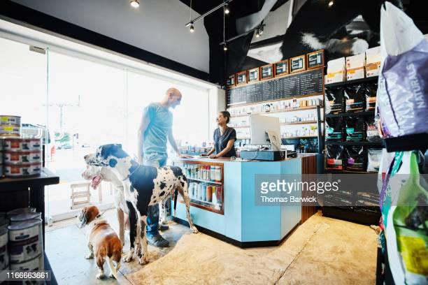 smiling pet store owner helping customer with dogs check out - finance and economy stock pictures, royalty-free photos & images