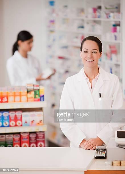 Sonriendo farmacéutico en farmacia parado en caja registradora