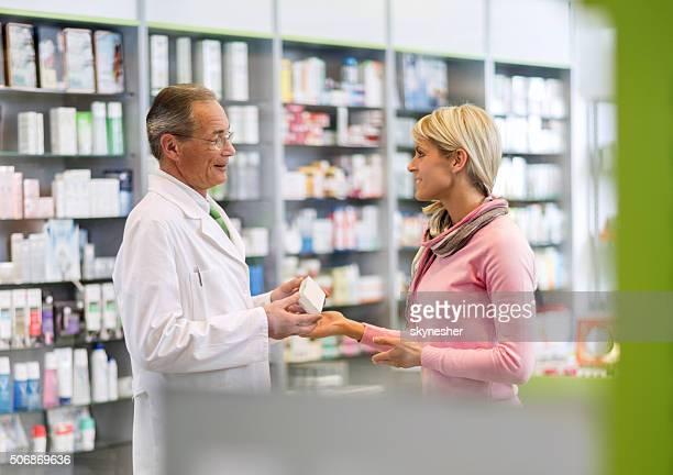 Lächelnd Apotheker im Gespräch mit junge Frau in der Apotheke.