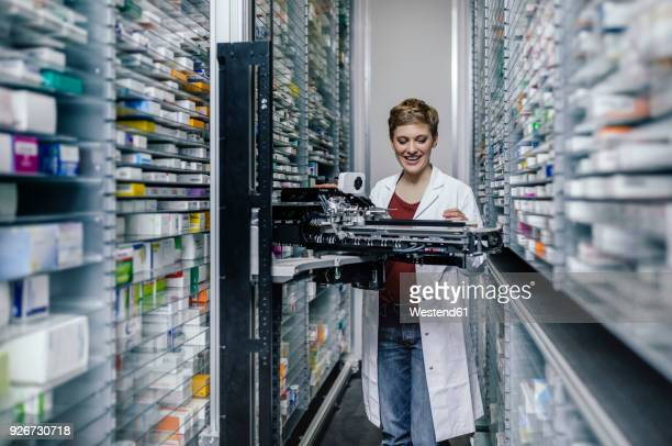 Smiling pharmacist with commissioning machine in pharmacy