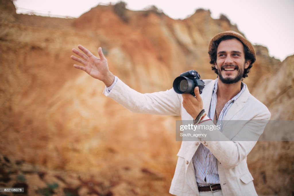 Smiling Photographer making pictures at the beach : Stock Photo