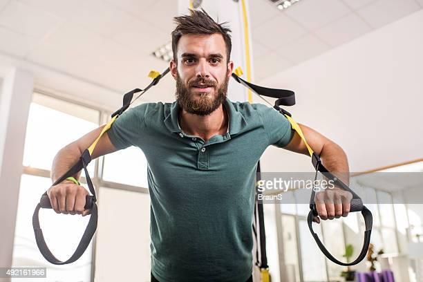 Smiling Pilates reformer exercising on Pilates machine at health club.