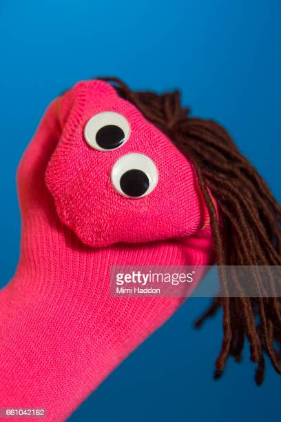 smiling pink sock puppet on blue seamless - googly eyes stock pictures, royalty-free photos & images